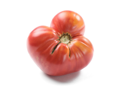 Imperfect big red heirloom tomato isolated closeup Stock Photo