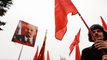 Orel, Rusland, 7 november 2017: Oktoberrevolutie jubileumvergadering. Hogere mens met rode vlag en portret Lening op achtergrond Redactioneel
