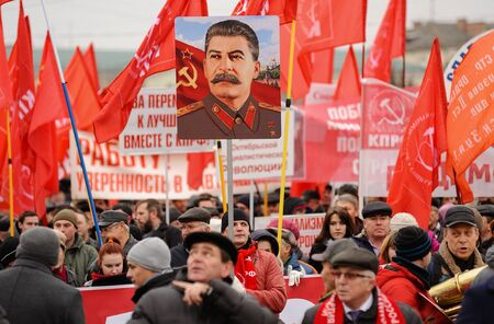 Orel, Russia, November 7, 2017: October Revolution anniversary meeting. Stalin portrait and many red Communist flags over crowd of people in dark clothes marching on the street