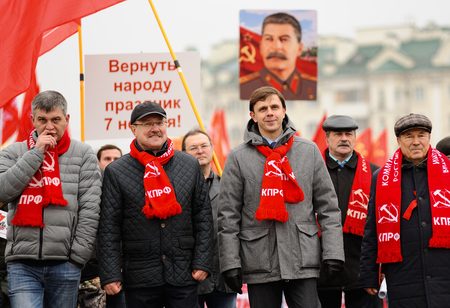 Orel, Russia, November 7, 2017: October Revolution anniversary meeting. Orel Governor Andrey Klychkov and Government members in red Communist scarves with Stalin portrait on the background