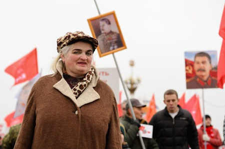 soviet flag: Orel, Russia, November 7, 2017: October Revolution anniversary meeting. Senior lady in bright makeup with Stalin portraits on background Editorial