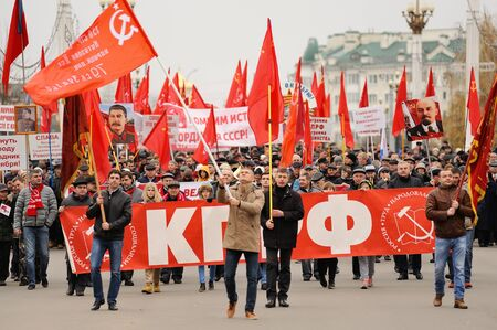 soviet flag: Orel, Russia, November 7, 2017: October Revolution anniversary meeting. Crowd of people marching with red Communist flags, banners, Lenin and Stalin portraits on the street