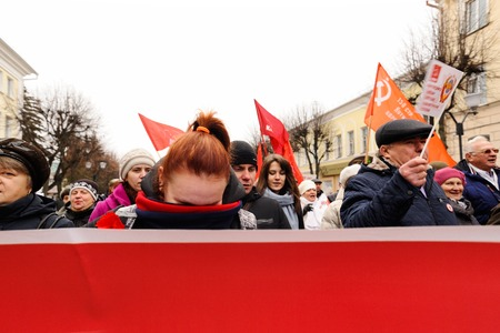 Orel, Russia, November 7, 2017: October Revolution anniversary meeting. Girl hides her face from camera behind red communist banner