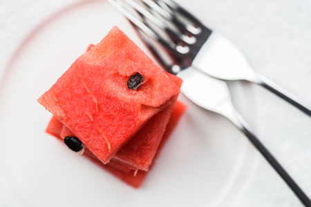 Watermelon pulp cut in squares with two forks. Low calorie vegan snack above view