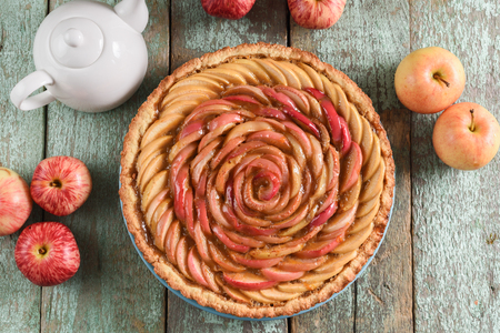 Beautiful homemade rose pie with raw apples on robin egg blue table. Rose made of apples overhead view Imagens