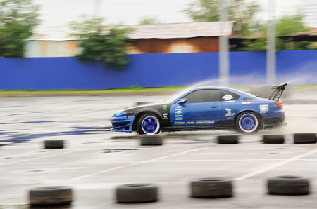 Orel, Russia, July 22, 2017: Dynamica car festival. Tuned car riding swiftly along tyre line  with water splashes motion blur