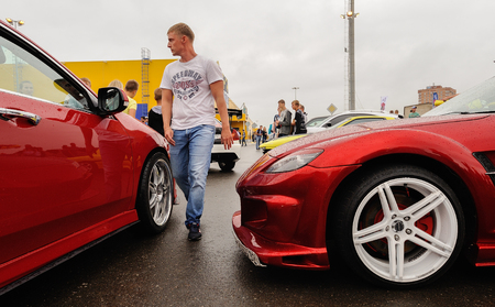Orel, Russia, July 22, 2017: Dynamica car festival. Tuned new red cars and wolking man