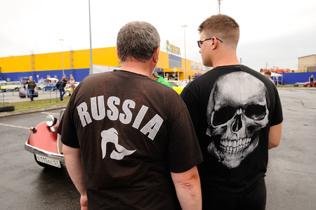 Orel, Russia, July 22, 2017: Dynamica car festival. Men standing their backs to camera in t-shirts Russia and skull closeup