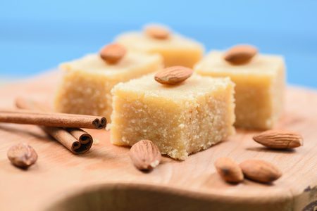 Indian traditional dessert, halva made with semolina and milk wih cinnamon and almonds on blue background close up Stock Photo
