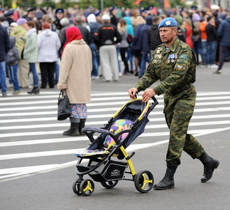 Orel, Russia - May 9, 2017: Celebration of 72th anniversary of the Victory Day (WWII). Man in paratrooper uniform with baby stroller square