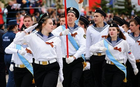 Orel, Russia - May 9, 2017: Victory Day selebration. Young people in white uniform shirts marching with flag