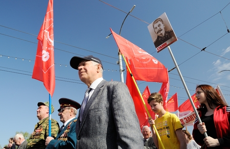 Orel, Russia - May 1, 2017: May demonstration. People marching with Stalin portrait and red Communist flags around