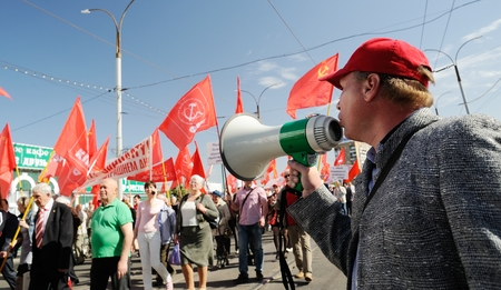 Orel, Russia - May 1, 2017: May demonstration. Man with loudspeaker talking to crowd with red Communist flags background
