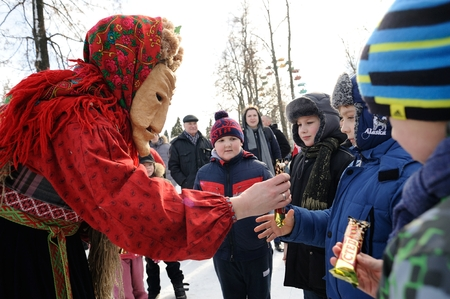 Orel, Russia - February 26, 2017: Maslenitsa fest. Woman at slavonic mask givin sweets to children closeup
