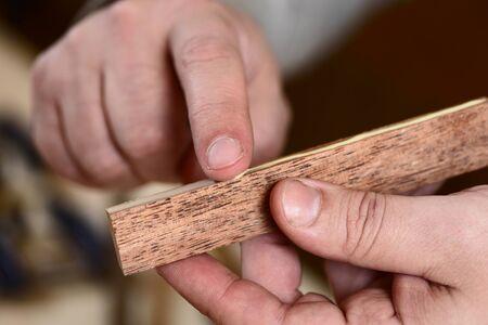 Carpenter použití lepidla na dřevěné prkno s holé ruce detailní