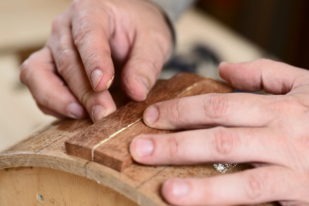 Carpenter glueing wooden parts for drum with bare hands closeup