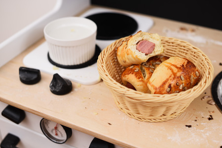 Homemade sausage rolls on toy kitchen for children play closeup Stock Photo