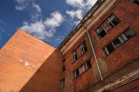 Abandoned red brick Soviet factory with broken windows and downpipe with blue sky