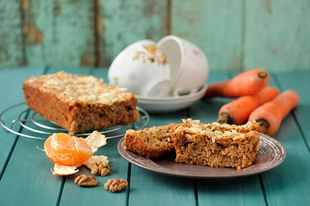 Homemade carrot cake with fresh carrots and clementines on turquoise background horizontal Stockfoto