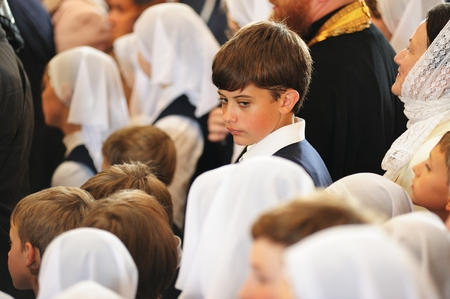 Orel, Russia - July 28, 2016: Russia baptism anniversary Divine Lutirgy. Boy among girls in white kerchieves selective focus