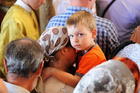 Orel, Russia - July 28, 2016: Russia baptism anniversary Divine Lutirgy. Little boy stairing in crowd of people Editorial