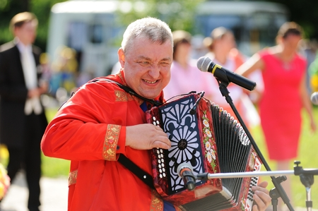 Orel, Russia - July 08, 2016: Russian Valentine Day  - Petr and Fevronia. Senior man in red outfit playing garmoshka, Russian accordion closeup