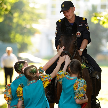 Orel, Russia - June 24, 2016: Turgenev Fest. Young Russian policeman on horse and little girls stroking it sqare