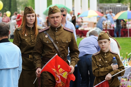 Orel, Russia - May 9, 2016: Celebration of 71th anniversary of the Victory Day (WWII). Family in soviet military uniform with red flags closeup Editorial