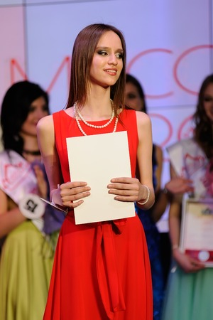 Orel, Russia - December 20, 2015: Miss Orel 2015 beauty contest. Brunette girl in red dress with diploma vertical