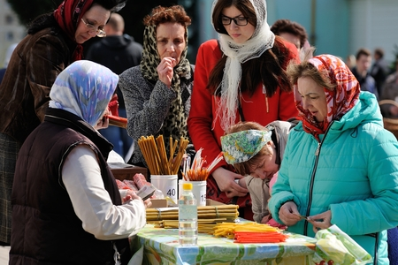 Orel, Russia - April 30, 2016: Paschal blessing of Easter baskets in Orthodox church. Women buying church candles closeup