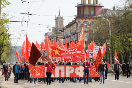 Orel, Russia - May 1, 2016: Communist party demonstration. People marching with red flags on empty street horizontal