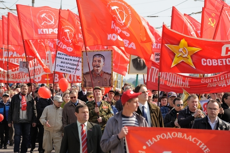 Orel, Russia - May 1, 2016: Communist party demonstration. People carrying red flags and Stalins portrait horizontal Editorial