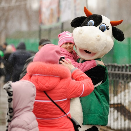 Orel, Russia - March 13, 2016: Maslenitsa, Pancake festival. Woman taking photo of child with cow doll  selective focus Éditoriale