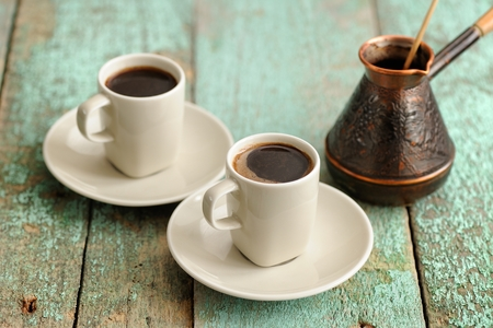 Two cups of fresh black coffee and copper cezve on old wooden table closeup
