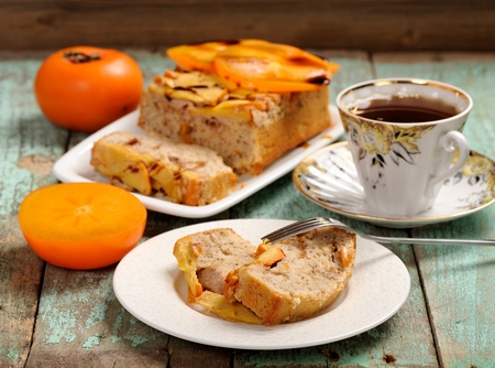 Persimmons cake with tea and fresh persimmons, chocolate sauce horizontal