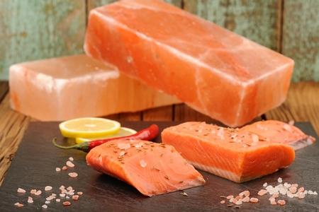 Wild salmon salted with himalayan pink salt blocks, lemon and chili closeup Banco de Imagens