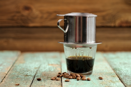 Vietnamese black coffee brewed in French drip filter on turquoise wooden table copyspace Фото со стока