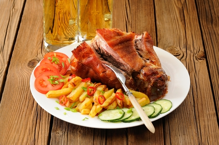 Cut eisbein with french fries, vegetables and beer closeup Stock Photo