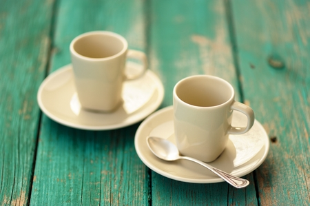 Two empty ebony espresso cups with silver spoon on turquoise shabby background horizontal