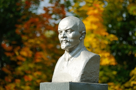 Lenin bust monument with autunm leaves on the background horizontal