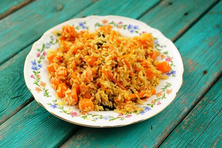 Vegetarian pumpkin pilaf in colored plate on wooden turquoise table closeup
