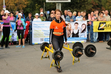 Orel, Russia, September 5, 2015: Girl carrying two heavy metal dumbbells in competition horizontal