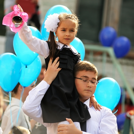 Orel, Russia - September 1, 2015: Young girl in school uniform rings a bell sitting on boys shoulders square Editorial