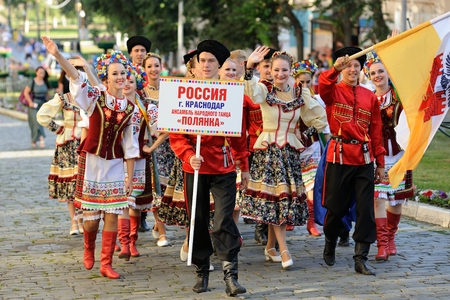 Orel, Russia, August 4, 2015: Orlovskaya Mozaika folk festival, men and women in traditional Cossack suits marching in the paved road horizontal