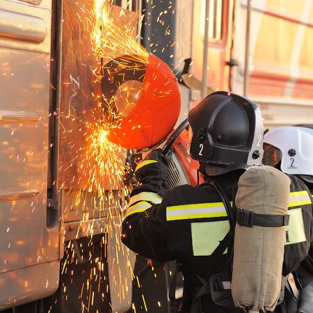 Orel, Russia - December 09, 2015: Emergency Control Ministry (MCHS) tactical exercise. Russian rescue team cutting carriage door with circular saw closeup