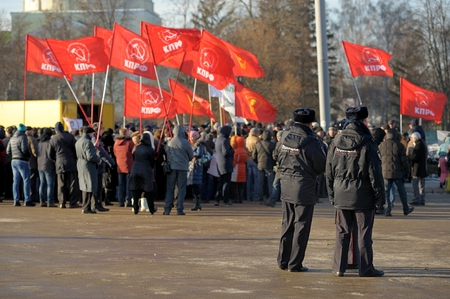 Orel, Russia - November 29, 2015: Russian truck drivers protest. Strikers with red flags and two policemen horizontal