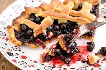 Piece of fresh homemade lattice pie with whole wild blueberries in white plate with fork closeup macro horizontal
