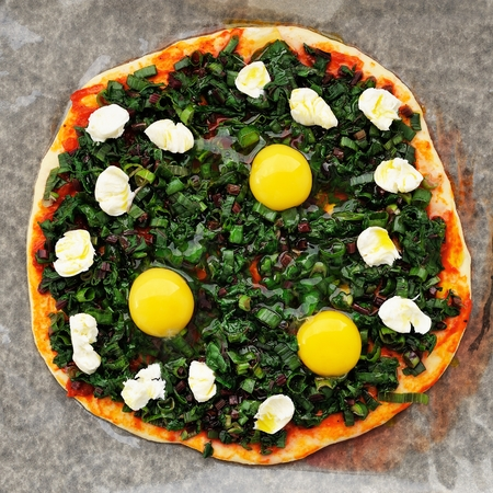 Raw round green pizza with chard, eggs and mozarella on baking paper top view square