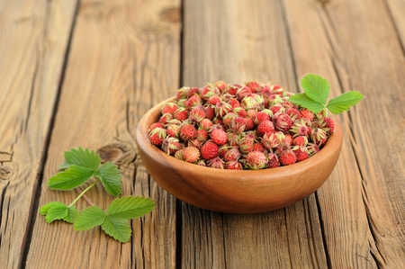 Wild strawberries Fragaria viridis with green leaves in wooden bowl on rustic wooden table copyspace