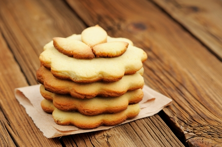 Four round sand cakes in pile decorated with three small leave cakes on craft paper close up selective focus closeup